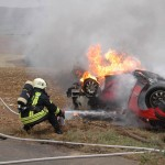 Löscharbeiten an einem brennenden PKW nach Unfall